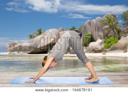 fitness, sport and people concept - woman doing yoga in downward facing dog pose on mat over exotic tropical beach background