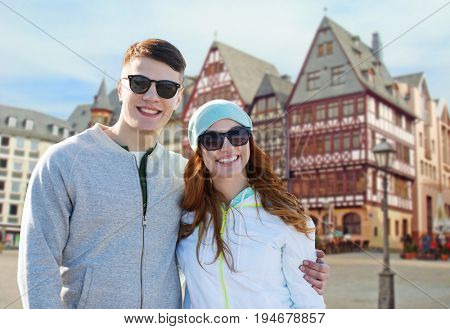 tourism, travel and people concept - happy teenage couple over frankfurt am main city street background