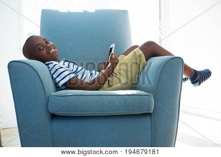 Side view portrait of smiling boy with mobile phone while lying on armchair in sitting room at home