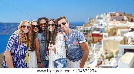 tourism, travel and people concept - smiling young hippie friends with selfie stick over oia town on santorini island background