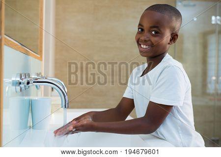 Portrait of smiling boy washing hands in sink at bathroom