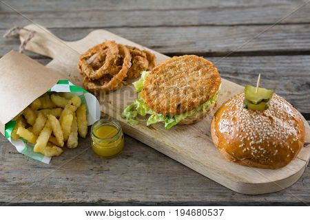 High angle view of burger with onion rings and french fries on table
