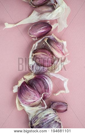 Garlic Cloves And Husks Close-up On A Soft Pink Background..