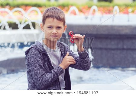 Child playing with a fidget spinner outdoors in city park