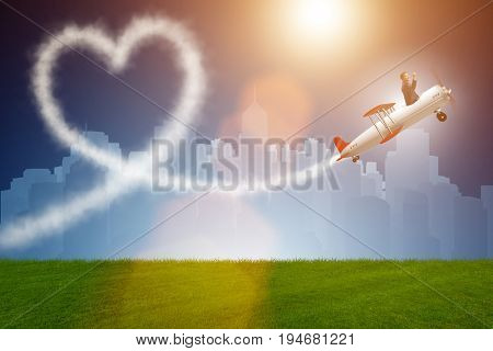 Man flying airplane and making heart shape