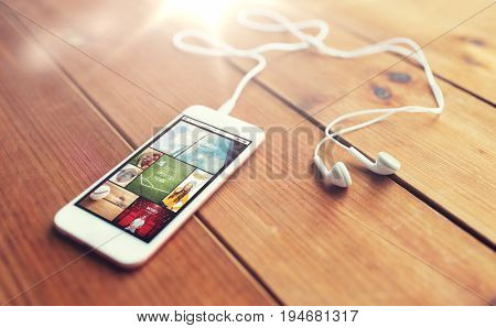 technology, music, gadget and object concept - close up of white smartphone and earphones on wooden surface with web applications on screen