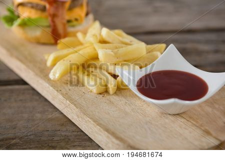 Close up of tomato sauce in bowl by french fries on cutting board