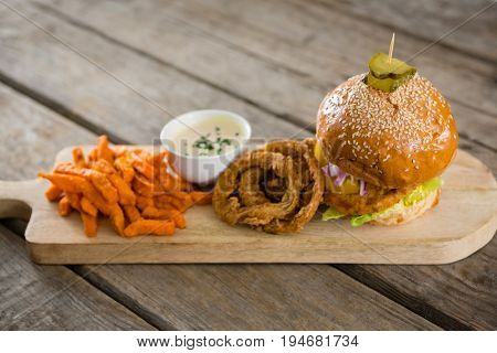 Hamburger by onion rings with dip and french fries on cutting board