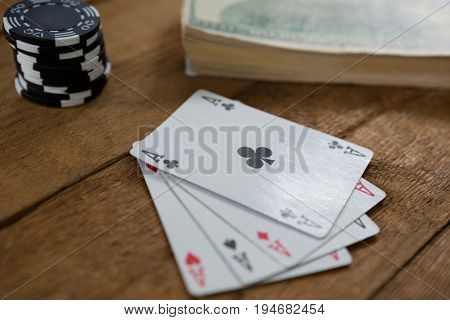 Close-up of four aces by chips and money on wooden table