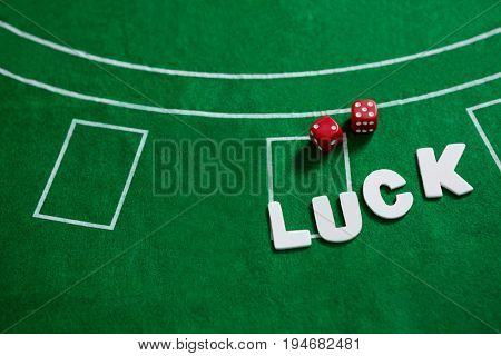 Close-up of text and red dices on blackjack table
