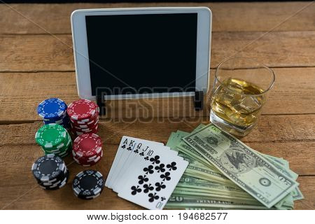 High angle view of digital tablet and whisky with currency on wooden table during poker game at casino