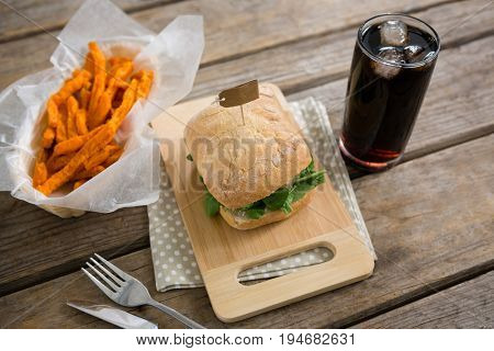 High angle veiw of burger with french fries and drink at table