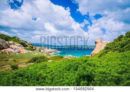 Costline with cloudscape and granite rocks and azure water near Porto Pollo, Sardinia, Italy.
