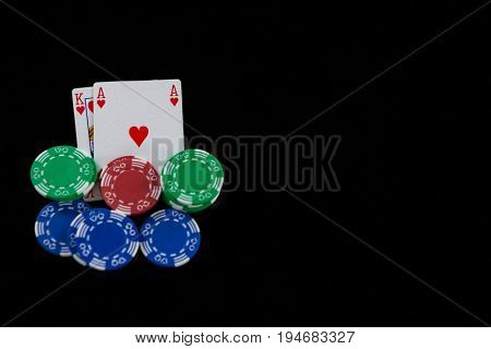 Close-up of cards and chips during blackjack game on black background