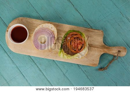 Overhead of hamburger and sauce on chopping board on wooden table