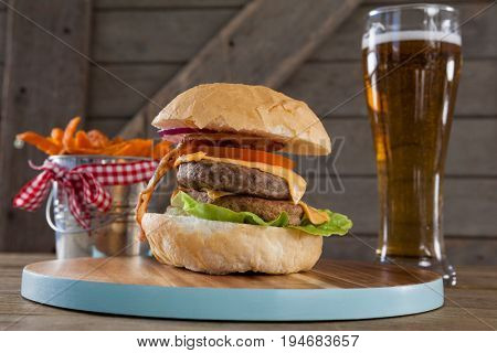 Hamburger, french fries and glass of beer on table against wooden background