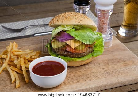 Close-up of hamburger, french fries and tomato sauce on chopping board