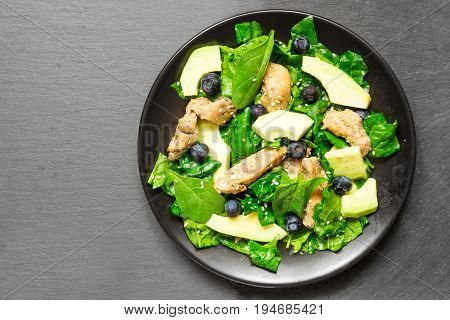 Chicken salad with avocado spinach and blueberries in black plate on gray stone background. high protein food. top view with copy space