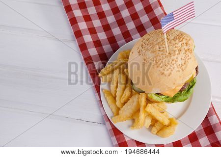 Overhead of burger decorated with american flag and french fries in plate