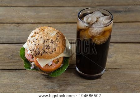 Hamburger and cold drink on table against wooden background