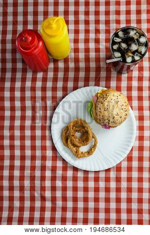 Overhead of hamburger, french fries, onion ring and cold drink on napkin