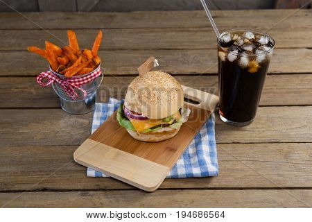 Hamburger, french fries and cold drink on table against wooden background