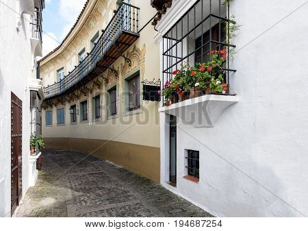 Old narrow street with beautiful balconies decorated with flower pots at traditional Spanish Village (Poble Espanyol)