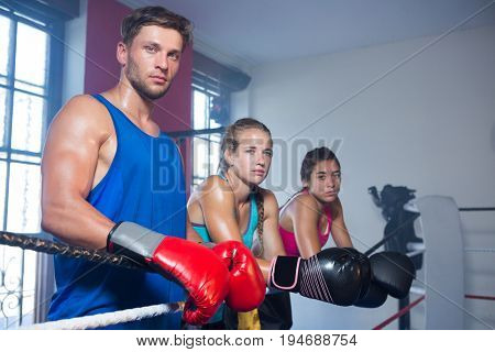 Portrait of young boxers standing by boxing ring rope