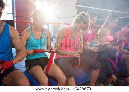 Back lit athletes sitting on boxing ring while wrapping bandages at fitness studio