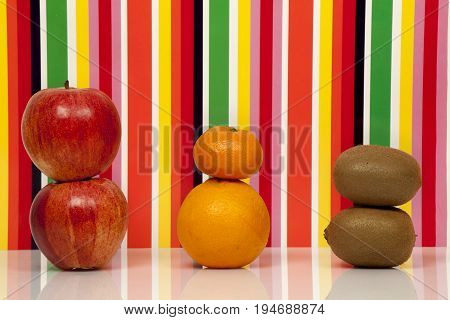 Fruits, multicolored background. Apple, orange, mandarin, kiwi. Two apples, an orange, a tangerine, two Kiwis are on a glossy surface with a background behind multicolored.