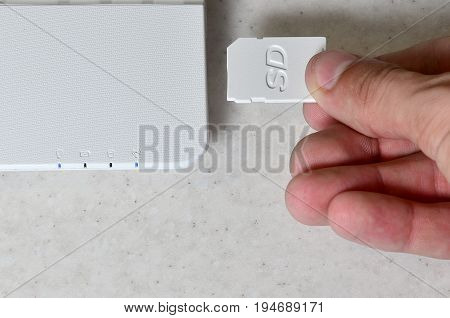 A Male Hand Inserts A White Compact Sd Card Into The Corresponding Input In The Side Of The White Ne