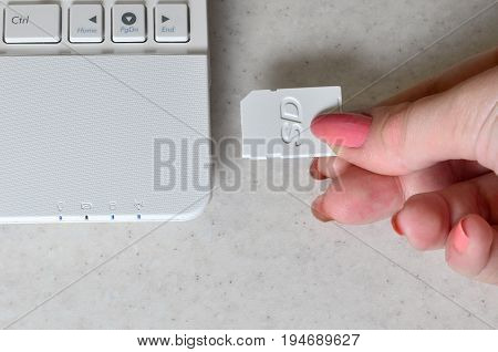 A Female Hand Inserts A White Compact Sd Card Into The Corresponding Input In The Side Of The White