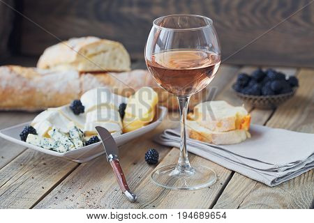 A glass of rose wine served with cheese plate blackberries and baguette. Assortment of cheese with berries on wooden background.
