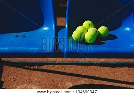 Tennis balls on blue plastic seats background