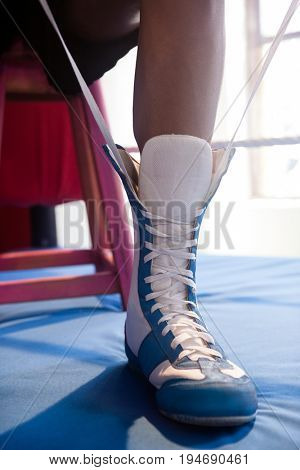 Low section of boxer wearing shoes in boxing ring