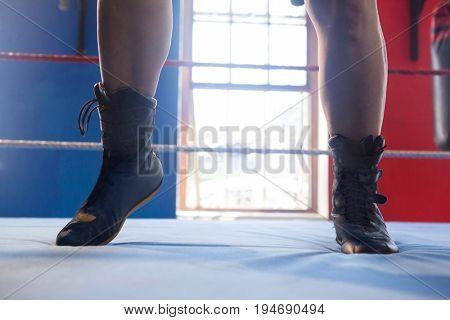 Low section of woman in boxing ring in fitness studio