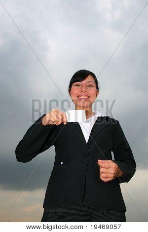 Asian woman under a cloudy sky.