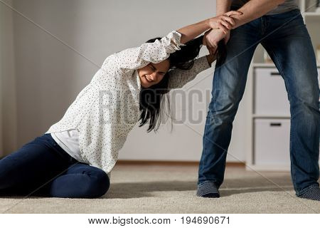 domestic violence, abuse and people concept - couple having fight and man dragging helpless woman by hair at home