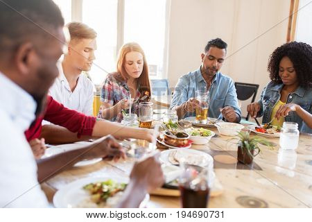 leisure, food and people concept - group of international friends eating at restaurant table