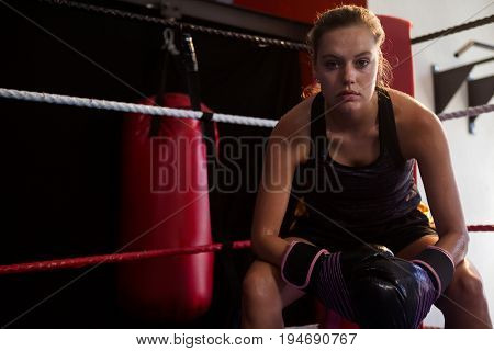 Portrait of confident woman sitting in boxing ring at fitness studio