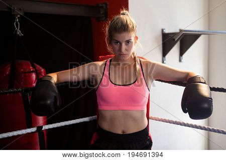 Confident woman sitting in boxing ring at fitness studio