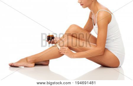 beauty, depilation, epilation, hair removal and people concept - beautiful woman with applicator applying depilatory wax to her leg over white background