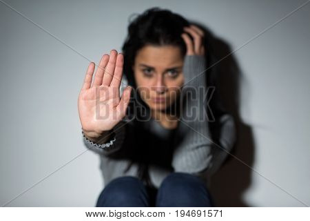 people and domestic violence concept - unhappy crying woman sitting on floor and showing defensive gesture