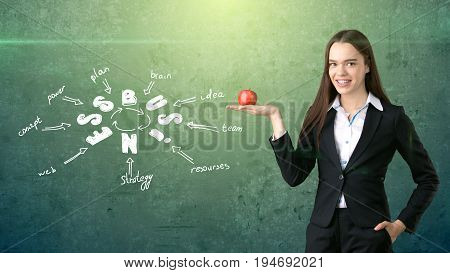 Woman In A Suit Holding Red Apple Standing Near Wall With Business Idea Sketch Drawn On It. Concept