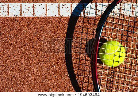 Tennis ball and a racket closeup on a tennis court