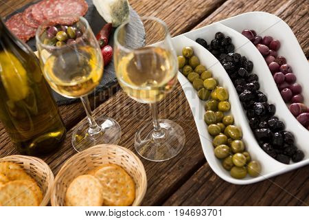 Close-up of marinated olives with bottle of wine and food on table