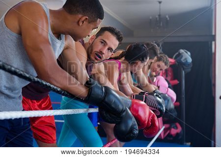 Tired male and female boxers leaning on rope in boxing ring