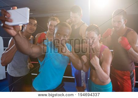Young boxers taking selfie in fighting stance standing at fitness studio
