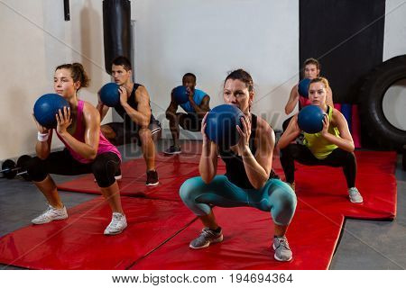 Young athletes crouching with exercise balls at fitness studio