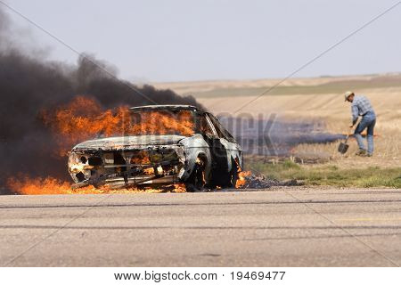 Car on fire while a man fights a grass fire